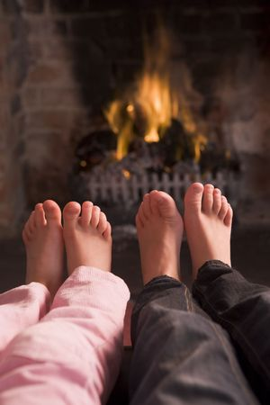 fireplace family: Childrens feet warming at a fireplace