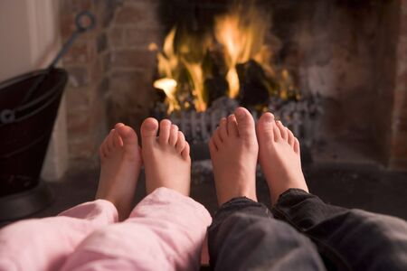 Couples feet warming at a fireplace photo