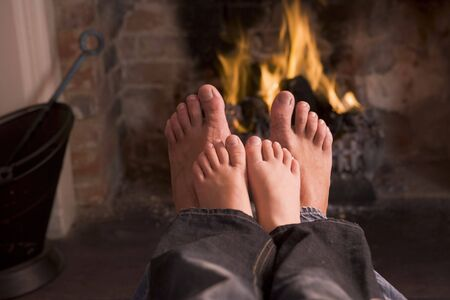 tranquil: Father and sons Feet warming at a fireplace Stock Photo