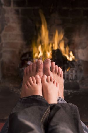 cosy: Father and sons feet warming at a fireplace Stock Photo