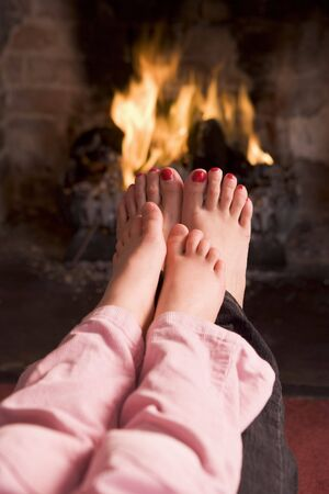 Mother and daughters Feet warming at a fireplace photo