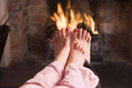 fireplace family: Mother and daughters feet warming at a fireplace