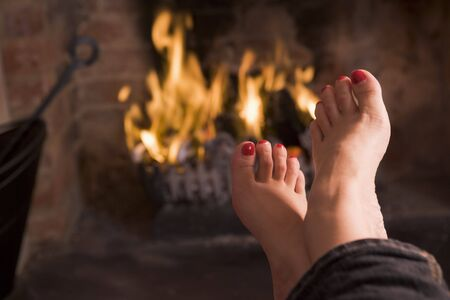 hearth and home: Feet warming at a fireplace