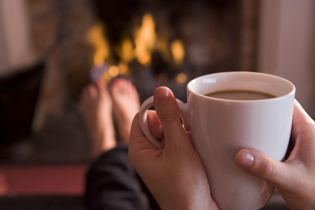 women holding cup: Feet warming at a fireplace with hands holding coffee