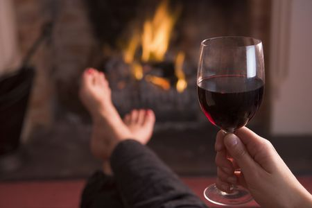 woman drinking wine: Feet warming at fireplace with hand holding wine Stock Photo