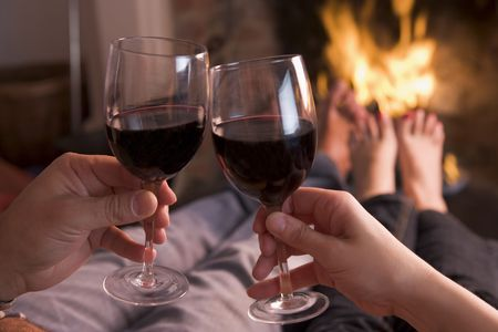 Feet warming at fireplace with hands holding wine photo