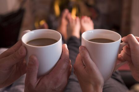 hombre tomando cafe: Pies en el calentamiento chimenea con las manos la celebración de café