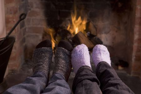 fireplace family: Couples feet warming at a fireplace