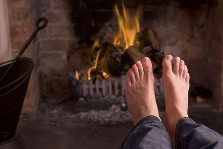 Feet warming at a fireplace photo