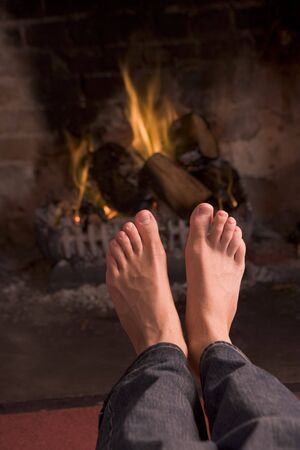 bare foot: Feet warming at a fireplace