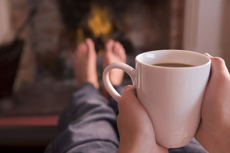 Feet warming at fireplace with hands holding coffee photo