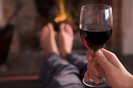 Feet warming at fireplace with hand holding wine photo