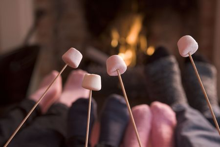 marshmallows: Feet warming at a fireplace with marshmallows on sticks Stock Photo