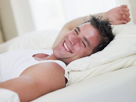 early 30s: Man lying in bed laughing Stock Photo