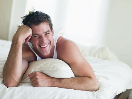 early thirties: Man lying in bed smiling
