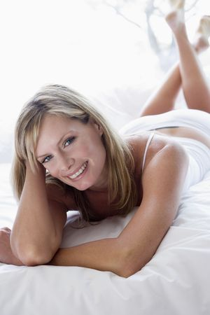 Woman lying in bed smiling Stock Photo - 3476456