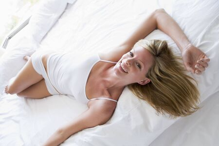 nightclothes: Woman lying in bed smiling