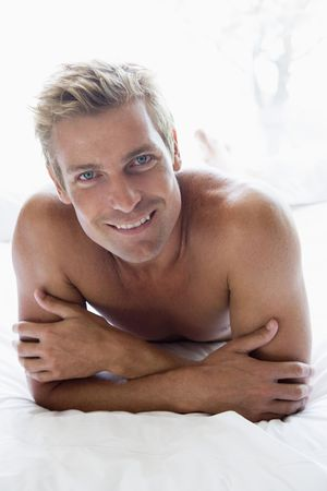 nightclothes: Man lying in bed smiling