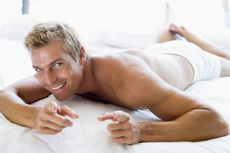 early 30s: Man lying in bed pointing and smiling