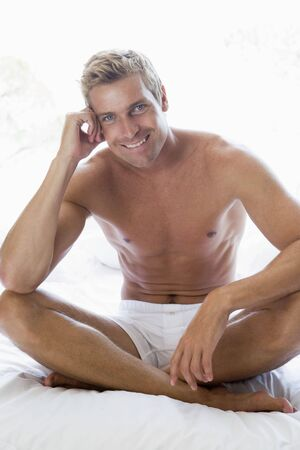 nightclothes: Man sitting on bed smiling