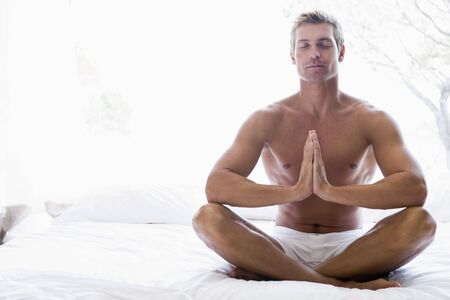 nightclothes: Man sitting on bed meditating