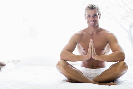 early thirties: Man sitting on bed meditating and smiling Stock Photo