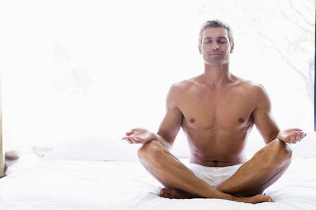 nightclothes: Man sitting on bed doing yoga Stock Photo