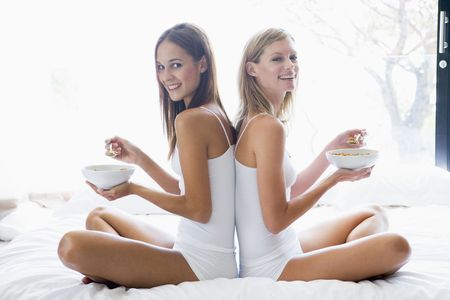 Two women sitting on bed eating cereal smiling photo