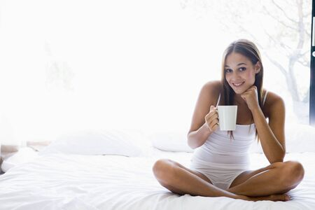 Woman sitting on bed drinking coffee smiling Stock Photo - 3476343
