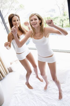 nightclothes: Two women jumping on bed smiling