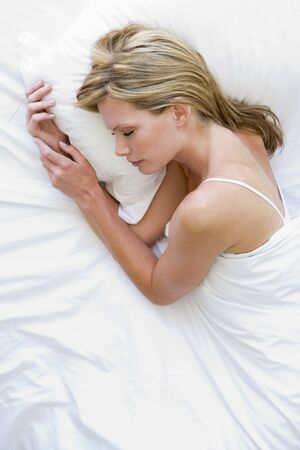 Woman lying in bed sleeping photo