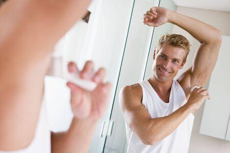 Man in bathroom applying deodorant smiling photo