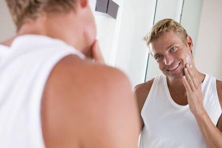 moisturiser: Man in bathroom applying face cream smiling