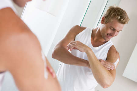 moisturiser: Man in bathroom applying lotion and smiling Stock Photo