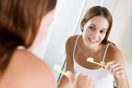 nightclothes: Woman in bathroom brushing teeth and smiling Stock Photo