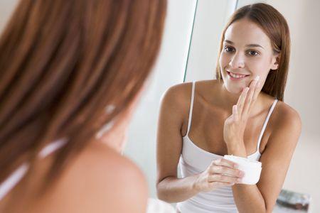 Woman in bathroom applying face cream smiling photo