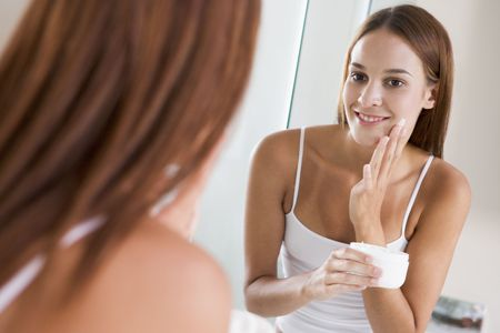 Woman in bathroom applying face cream smiling photo