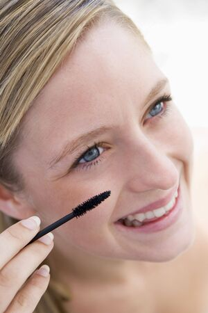 Woman with mascara wand smiling photo