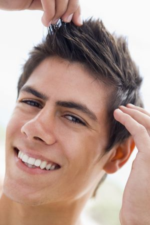 hair product: Man playing with hair smiling