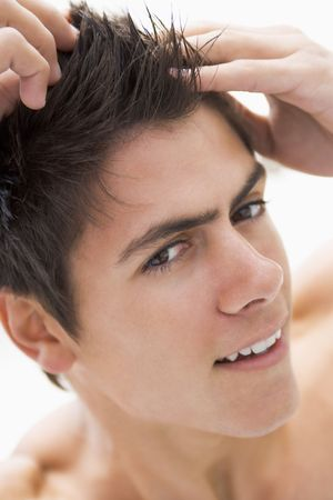 male grooming: Man playing with hair smiling