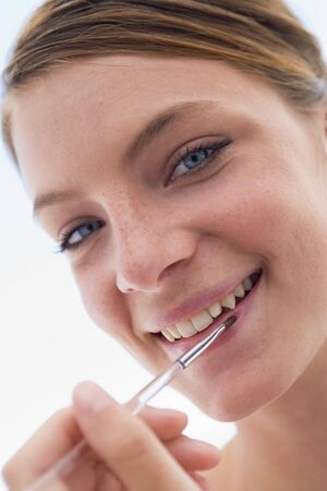 Woman with lipgloss applicator smiling photo