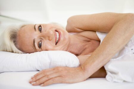 sexy mature women: Woman lying in bed smiling