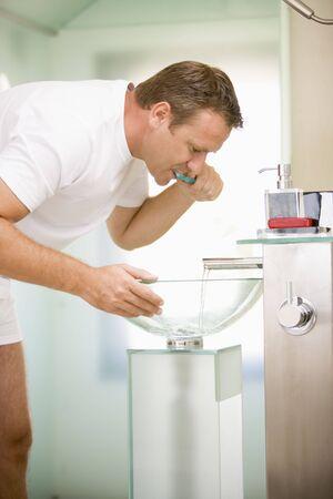 Man in bathroom brushing teeth photo