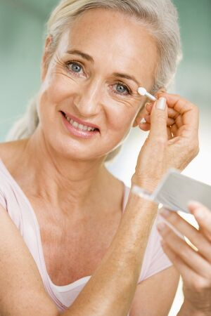 Woman applying eye makeup and smiling photo