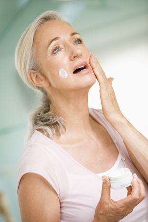 Woman applying face cream photo