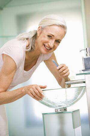 Woman in bathroom brushing teeth smiling photo