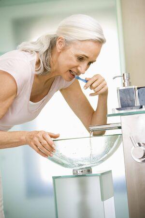 Woman in bathroom brushing teeth photo