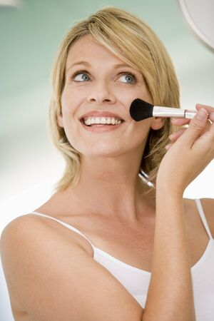 Woman with makeup brush smiling photo