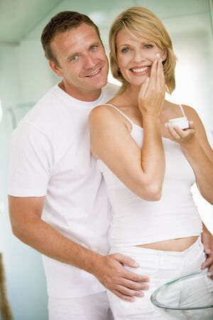 nightclothes: Couple in bathroom with face cream smiling