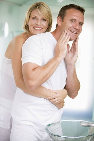 Couple in bathroom embracing and smiling photo